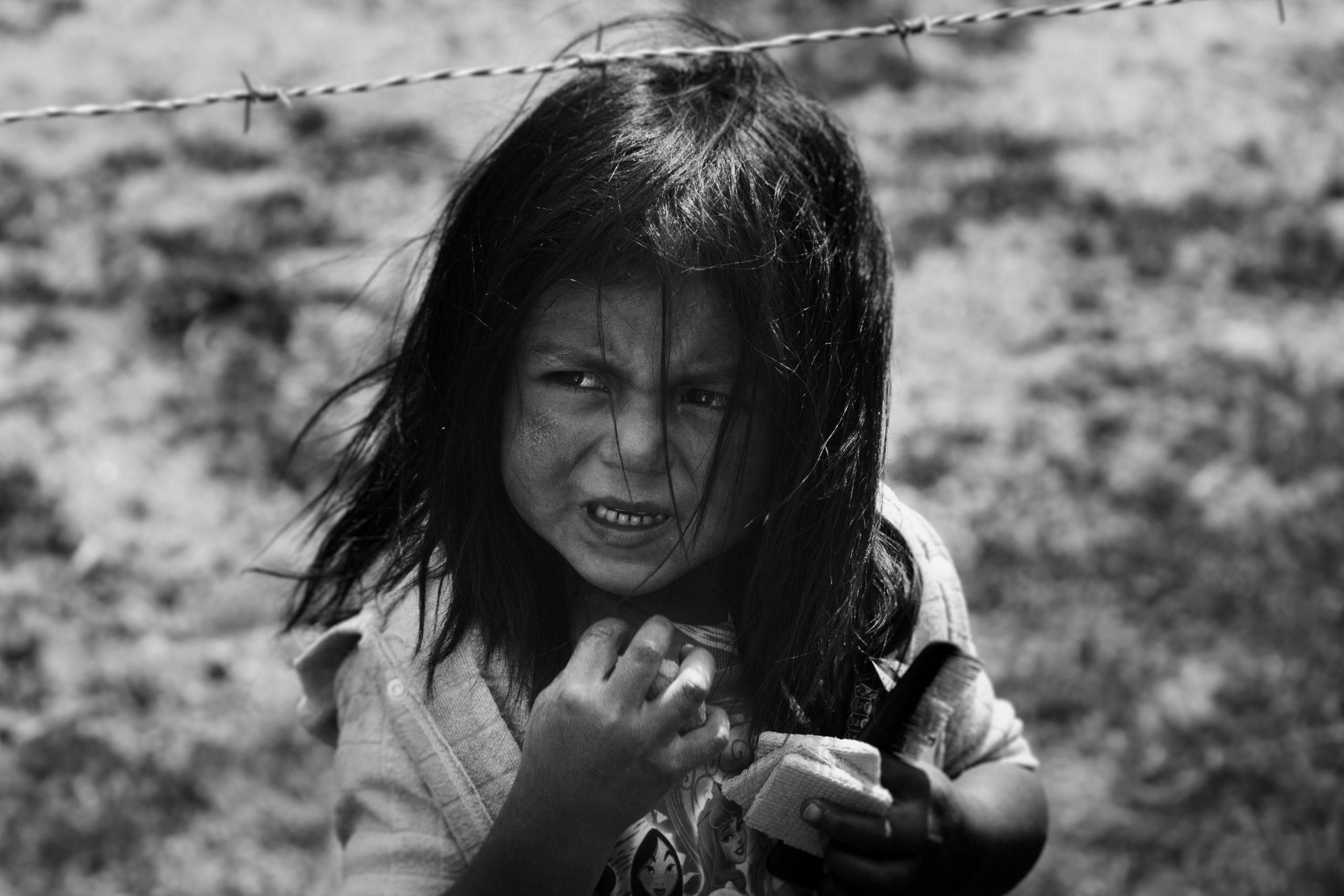 Young girl by barbed wire fencing
