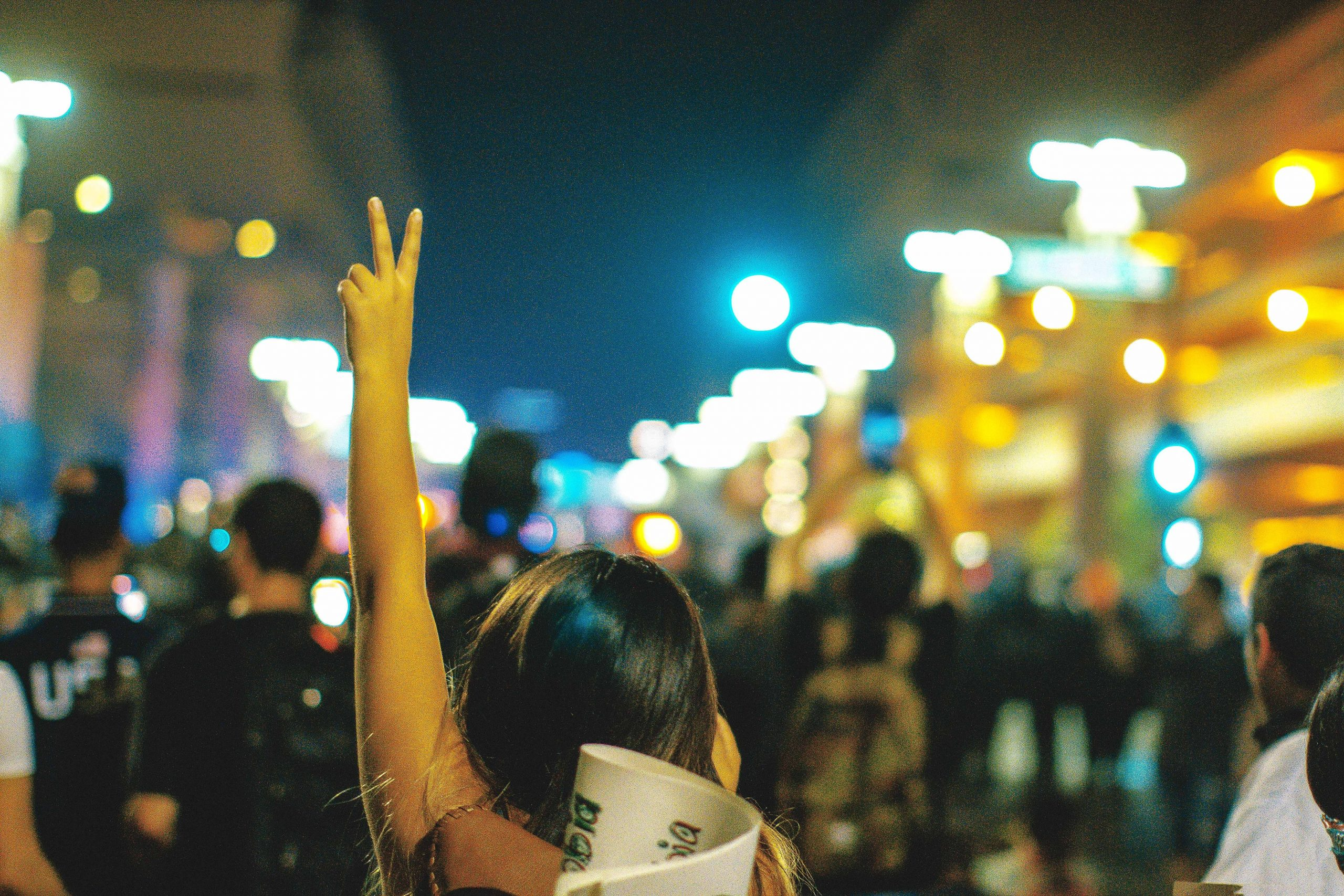 Girl with hand in a peace sign at a protest or march