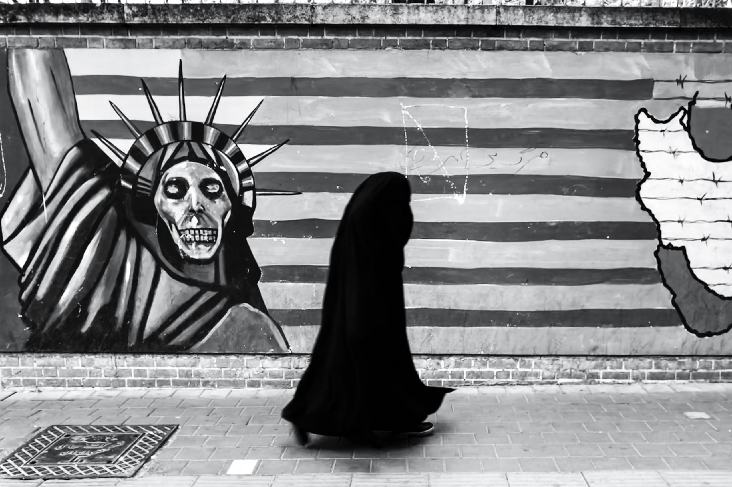 Muslim women walking by Statue of Liberty graffiti